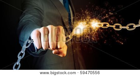 Powerful businessman holding chain in his fist