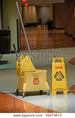 Mop and Bucket with caution sign on wet floor