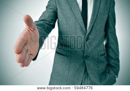 man wearing a suit offering to shake hands