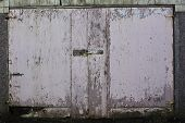 Faded pink, weather beaten, garage door, with paint peeling and rusting hinges and lock. poster