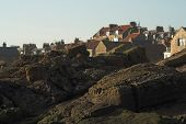 Anstruther (near St.Andrews) rocky coastline looking back towards the village. poster