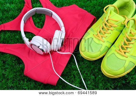 Sport clothes, shoes and headphones on green grass background poster