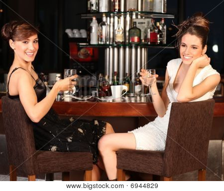 Two Beautiful Young Women Drinking Water At Bar