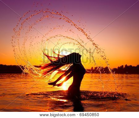 Beauty Model Girl Splashing Water with her Hair. Teen girl Swimming and splashing on summer beach over sunset. Beautiful Woman in Water