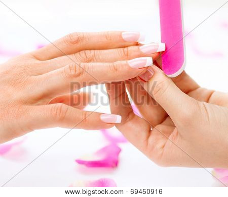 Manicure and Hands Spa. Woman in a Beauty Nail Salon receiving a manicure by a beautician. Gentle care of nails in a beauty salon. Nail file. Manicure process