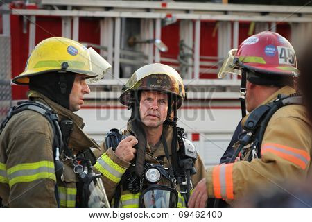MONTREAL  CANADA - AUGUST 01: Unidenfity lieutenant firefighter in front of firetruck discussing with the firefighters on august 01, 2014 in MONTREAL
