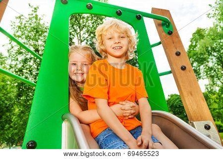 Boy and girl behind hug on chute with smile