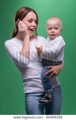 Mother holding toddler son with toy phone