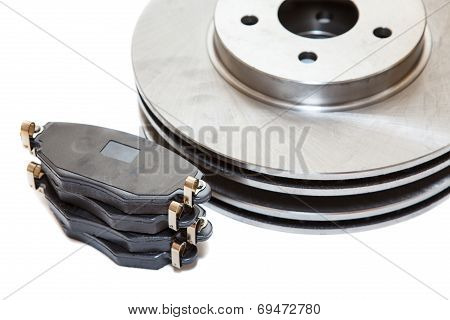 Two Brake Disks And Pads Isolated On White Background