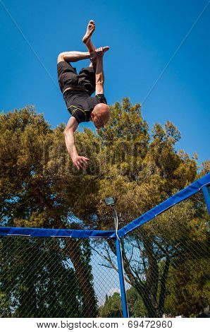 A Man Trick Jumping On A Trampoline