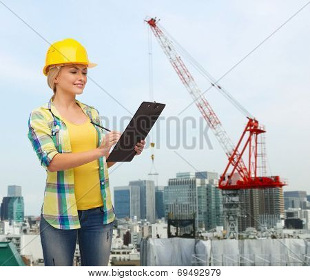 repair, building, construction and maintenance concept - smiling woman in helmet with clipboard making notes