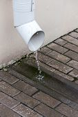 Rain water flowing from a metal drain pipe poster