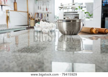 Mixing bowl with eggs and rolling pin on marble countertop in commercial kitchen poster