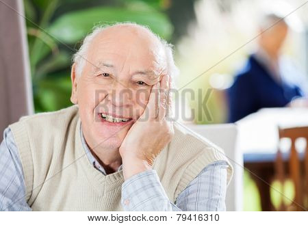 Portrait of happy senior man sitting at nursing home with grandson in background