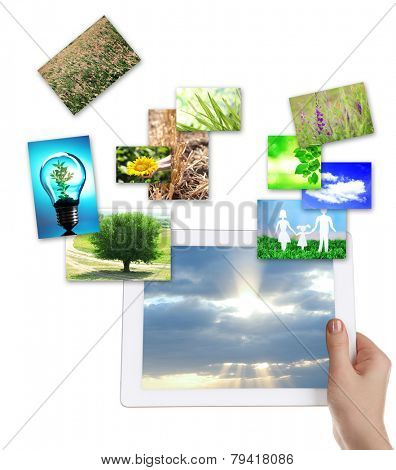 Tablet PC in hand and images of nature objects isolated on white