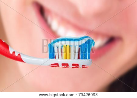 Red Toothbrush With Blue Two Color Toothpaste On Human Smile Background