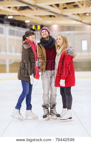 people, friendship, technology and leisure concept - happy friends taking picture with smartphone and selfie stick on skating rink