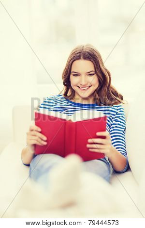 leasure and home concept - smiling teenage girl woman reading book and sitting on couch at home