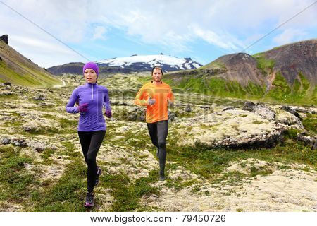 Sport running. Runners on cross country trail outdoors working out for marathon. Fit young fitness model man and asian woman training together outside in mountain nature on Snaefellsnes, Iceland. poster