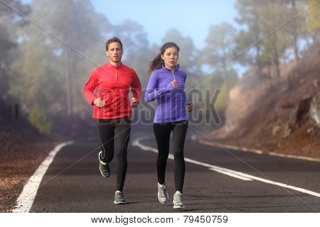 Healthy running runner man and woman workout on mountain road. Jogging male and female fitness model working out training for marathon on forest road in amazing nature landscape. Two runners