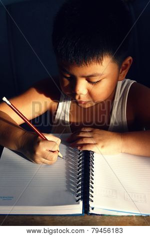 Young asian boy writing on a notebook
