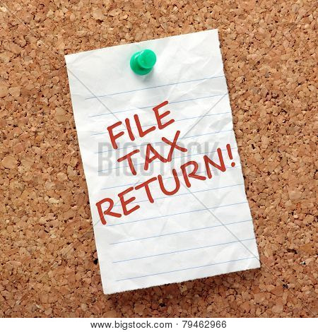 A reminder note to finish and file your tax return on a piece of crumpled, lined paper pinned to a cork notice board poster