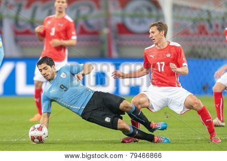 KLAGENFURT, AUSTRIA - MARCH 05, 2014: Florian Klein (#17 Austria) and Luis Suarez (#9 Uruguay) fight for the ball in a friendly soccer game between Austria and Uruguay.