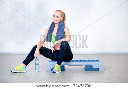 Fitness woman resting after exercises in gym