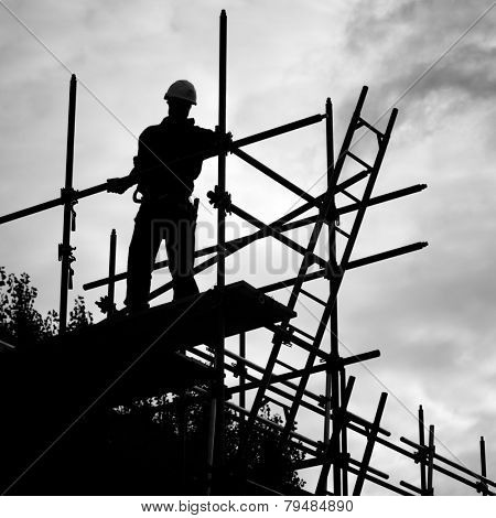 silhouette of construction worker against sky on scaffolding with ladder on building site.Monochrome