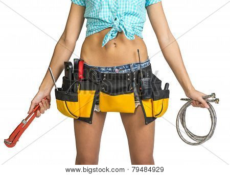 Plumber in shorts, shirt, tool belt with tools holding flexible hose and wrench