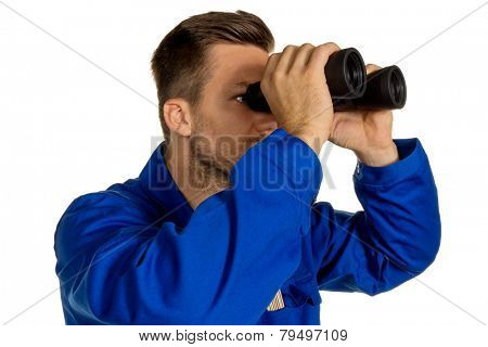 a worker in an industrial enterprise (craftsmen) with binoculars looking for jobs or jobs