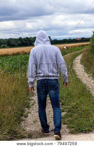 a man walks alone on a path.