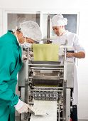 Chefs processing ravioli pasta in machine at commercial kitchen poster