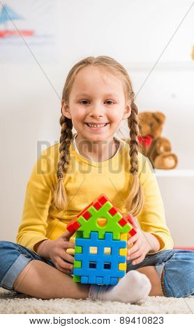 Little pretty smiling girl in yellow pullover holding lego house. poster