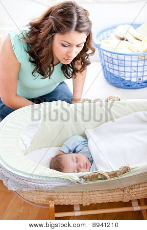 Young Mother Looking At Her Little Son Sleeping In His Bed