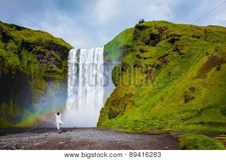 Grand waterfall with rainbow in the water mist Skogafoss. Elderly woman performs asana