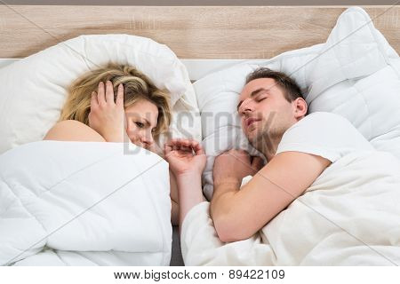 Woman Covering Ears While Man Snoring