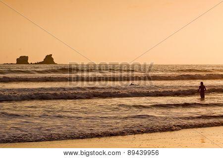 Unidentified tourists enjoying the ocean during sunset, Puerto Lopez, Ecuador