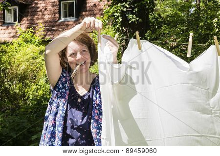 Woman Hanging Up The Washing In A Garden