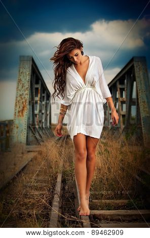 poster of Sensual girl with white dress walking on the railway under the blue sky. Beautiful woman with long hair and bare feet, outdoor shot over cloudy sky