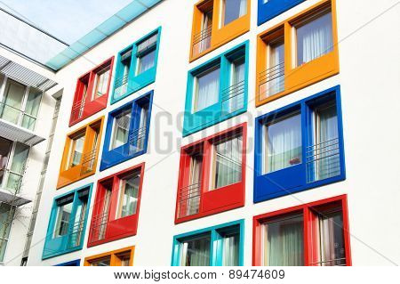 colorful facade of a modern apartment building, symbol of housing, rental, anonymity, city poster