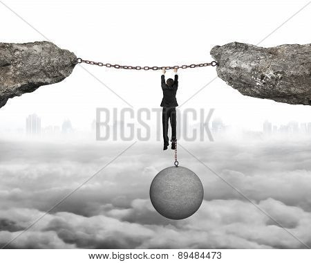 Businessman Shackled By Ball Hanging On Iron Chains Connected Cliffs