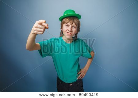 Boy teenager European appearance in green hat shows his finger f