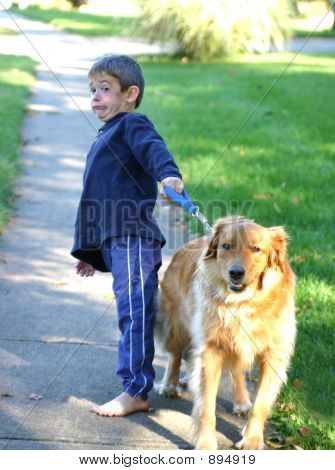 boy walking dog trying to keep her from running poster