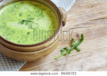 Green Vegetable Soup In A Brown Bowl On Rustic Wood