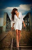 Sensual girl with white dress walking on the railway under the blue sky. Beautiful woman with long hair and bare feet, outdoor shot over cloudy sky poster