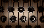 """Sepia-toned close up of old manual typewriter keyboard with scratched chrome keys that spell out """"THE END"""" on two rows. Lighting and focus are centered on """"THE END"""" keys. poster"""