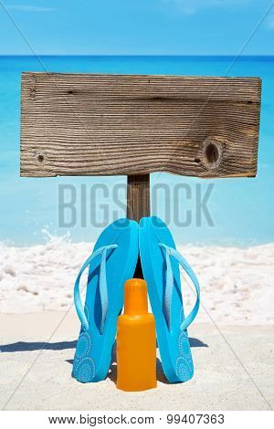 Wooden signboard with copy space and flip flops with a bottle suntan lotion on the sunny beach poster