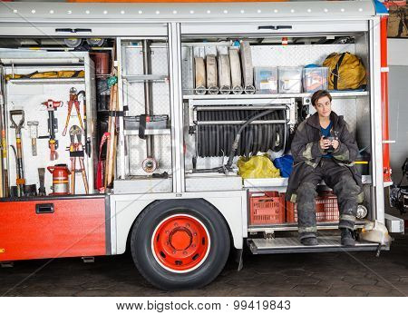 Full length of firewoman holding coffee mug while sitting in truck at fire station