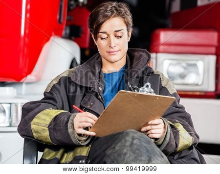 Young firewoman writing on clipboard while sitting against trucks at fire station